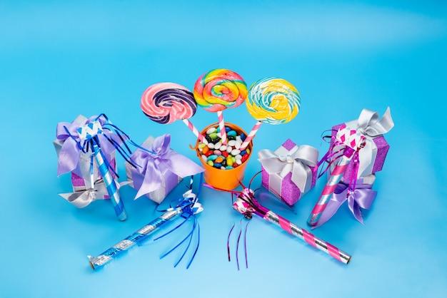 Una vista superior de paletas y regalos alogn con dulces multicolores silbatos de cumpleaños sobre el fondo azul confitura de azúcar dulce caramelo