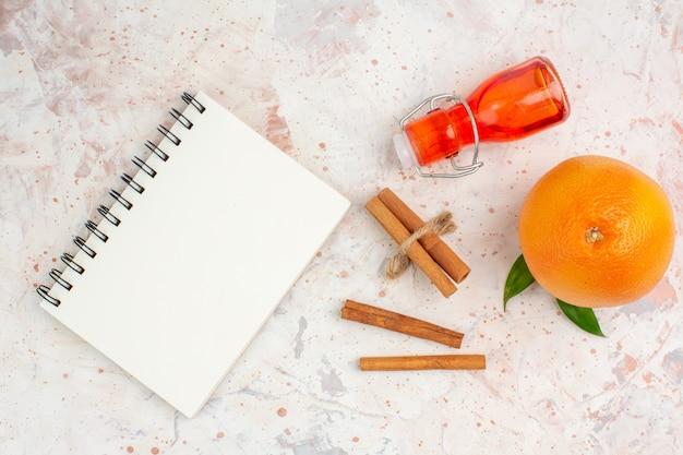 Vista superior de palitos de canela naranja fresca embotellar un cuaderno en una superficie brillante