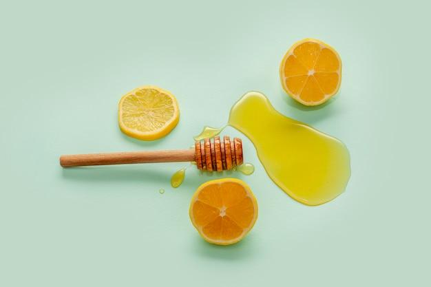 Vista superior de palitos de miel y rodajas de limón