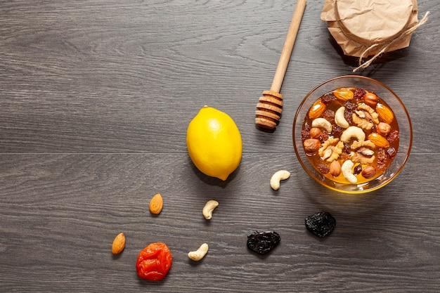 Vista superior palo de miel y tazón con nueces