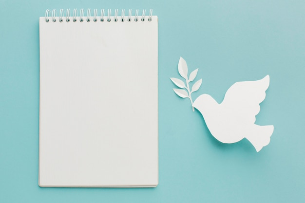 Vista superior de paloma de papel con cuaderno