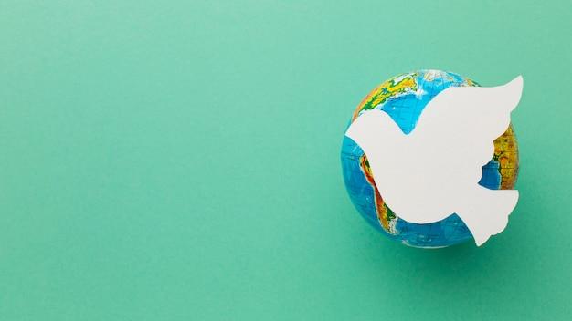 Vista superior de la paloma de papel en globo terráqueo