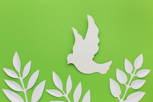 Vista superior de paloma de papel y hojas