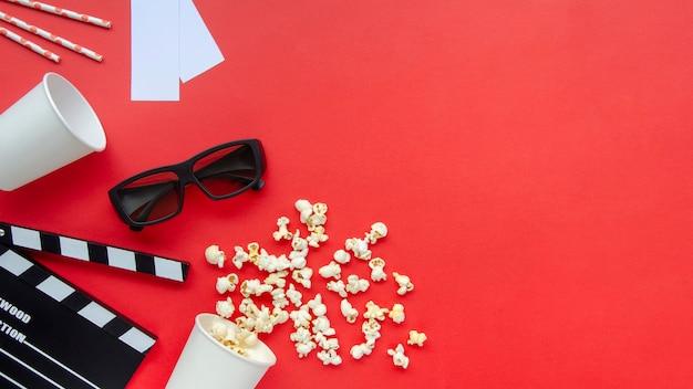Vista superior de palomitas de maíz con claqueta de cine sobre la mesa