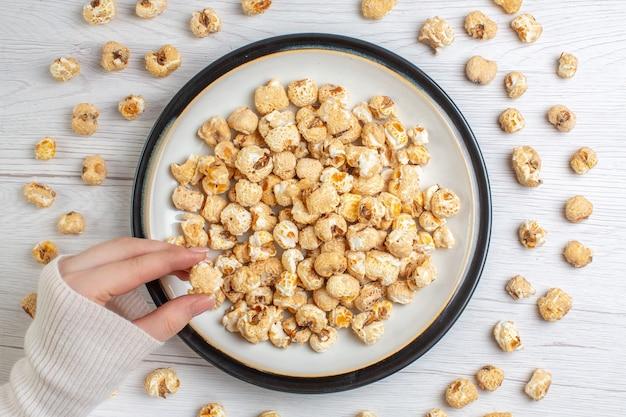Vista superior de palomitas de maíz dulce dentro de la placa sobre superficie blanca