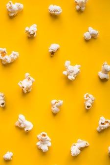 Vista superior de palomitas de maíz sobre fondo amarillo