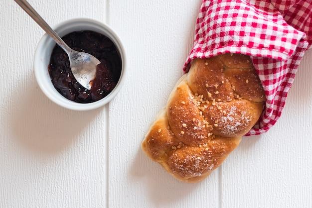 Vista superior de pan dulce y mermelada en mesa de madera