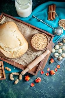 Vista superior de pan fresco con huevos y leche en la superficie azul oscuro