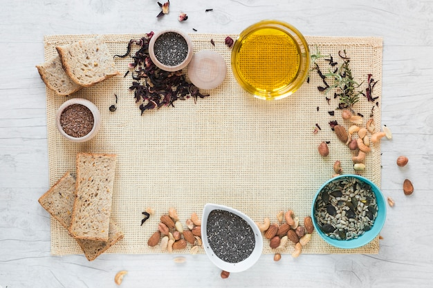 Vista superior del pan y los ingredientes saludables dispuestos en mantel