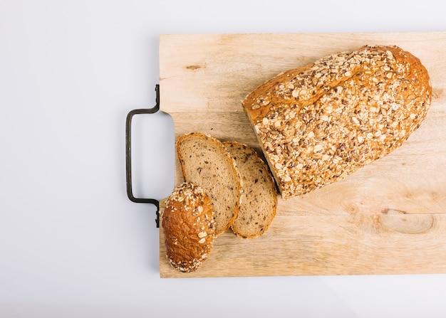 Vista superior del pan integral en rodajas en la tajadera sobre fondo blanco