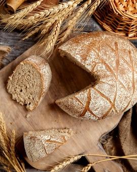 Vista superior de pan integral y sus rebanadas servidas en estilo rústico