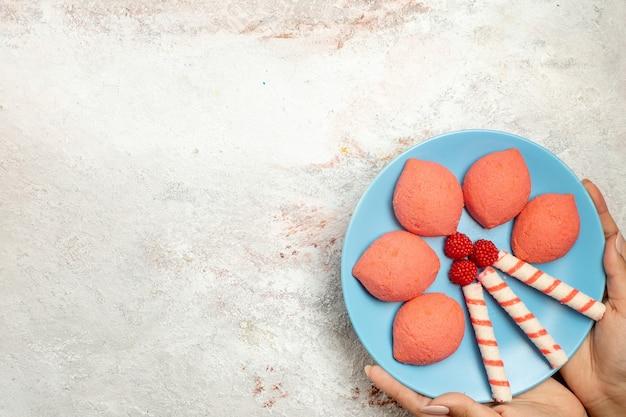Vista superior de pan de jengibre de color rosa dentro de la placa sobre fondo blanco claro pastel galleta pastel dulce galleta de azúcar