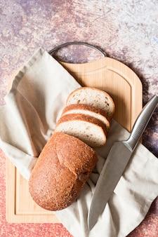 Vista superior de pan de molde con tabla de cortar y cuchillo
