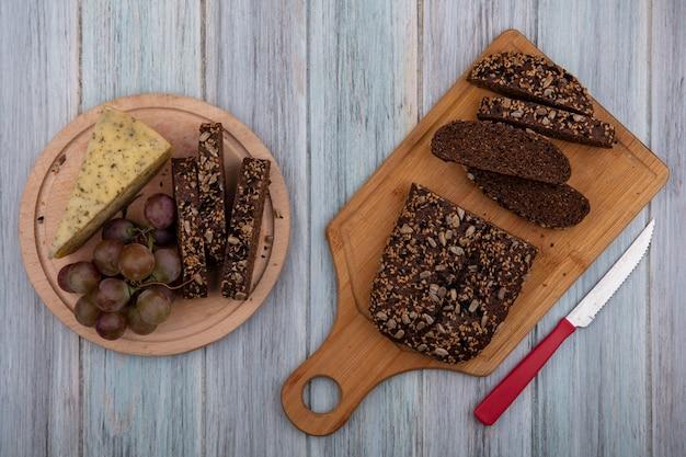 Vista superior de pan negro con un cuchillo en una tabla con uvas y queso en un soporte sobre un fondo gris