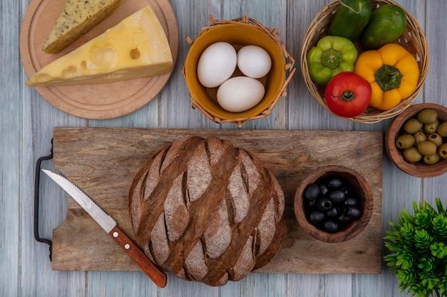 Vista superior de pan negro en un soporte con huevos de gallina, tomate, pimientos, pepinos, queso y aceitunas.