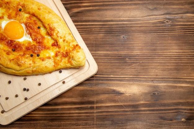 Vista superior pan recién horneado con huevo cocido sobre fondo de madera marrón masa desayuno huevo bollo comida