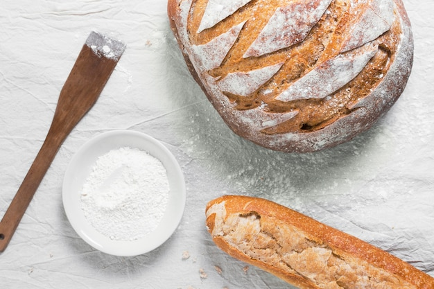 Vista superior de pan redondo y baguette francés con harina