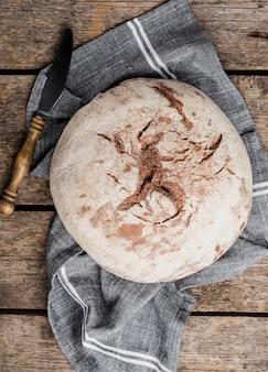 Vista superior de pan redondo con cuchillo sobre tela