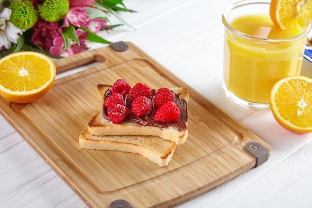 Vista superior de pan tostado con mantequilla de maní, frambuesas y plátanos