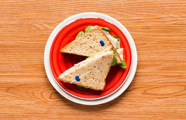 Vista superior de pan tostado saludable con lechuga sobre un fondo de madera
