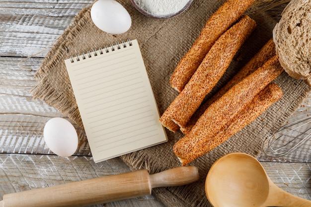 Vista superior de panadería con bloc de notas, huevos, rodillo sobre tela de saco y superficie de madera. horizontal