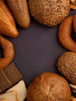 Vista superior de panes como baguette cob bagel blanco y negro sobre fondo granate con espacio de copia