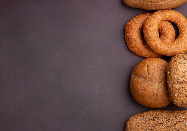 Vista superior de panes como baguette de mazorca de bagel en el lado derecho y fondo granate con espacio de copia