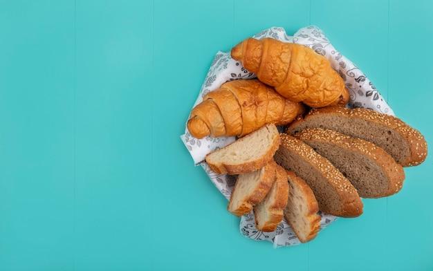 Vista superior de los panes como baguette de mazorca sin semillas en rodajas y croissant en un tazón sobre fondo azul con espacio de copia