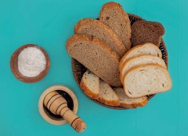 Vista superior de panes como baguette en rodajas sembrado mazorca marrón y centeno en una canasta con harina y pimienta negra sobre fondo azul.
