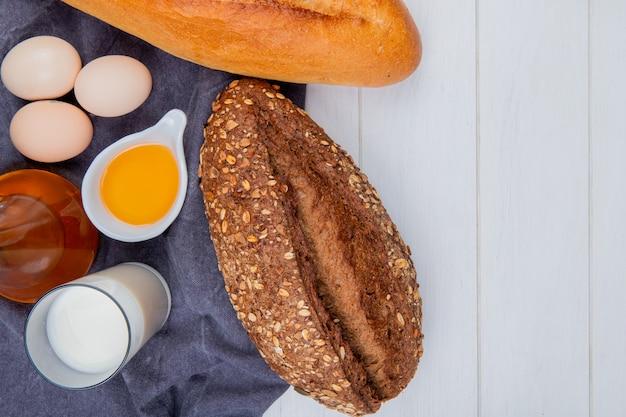 Vista superior de panes como baguette vietnamita y con semillas negras con huevos mantequilla leche sobre tela gris sobre fondo de madera con espacio de copia