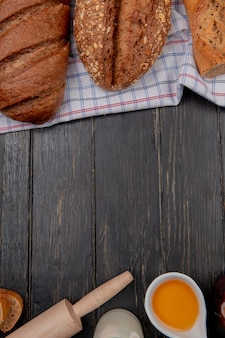 Vista superior de panes como baguettes vietnamitas sembradas y pan negro sobre tela con mantequilla rodillo de leche sobre fondo de madera con espacio de copia