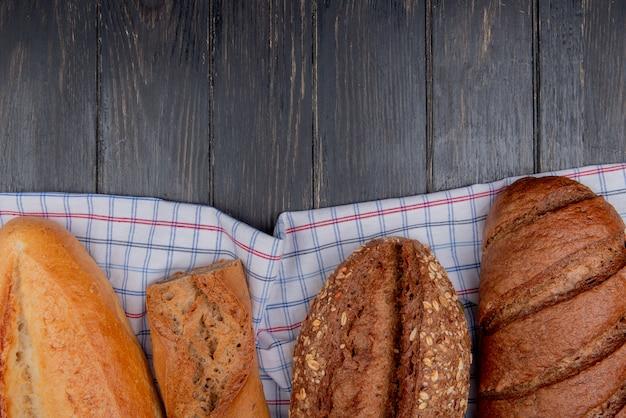 Vista superior de panes como baguettes vietnamitas con semillas francesas y pan negro sobre tela escocesa y fondo de madera con espacio de copia