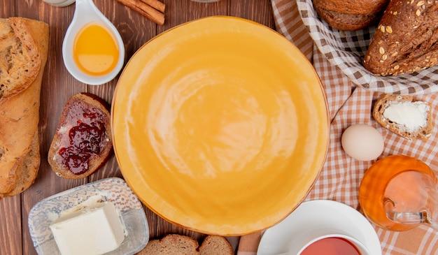 Vista superior de panes como crujientes baguettes sembradas rebanadas de pan de centeno con mermelada de mantequilla té de huevo canela alrededor de la placa sobre fondo de madera