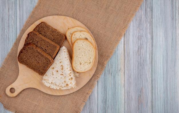 Vista superior de panes como pan blanco de centeno en rodajas y pan plano en tabla de cortar sobre tela de saco sobre fondo de madera con espacio de copia