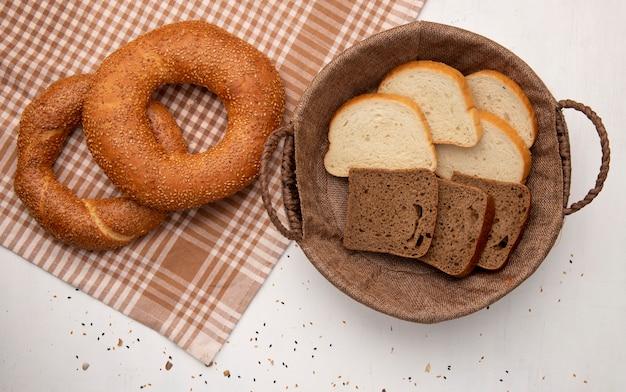 Vista superior de panes como panecillo turco sobre tela y canasta con rebanadas de pan blanco y centeno sobre fondo blanco.