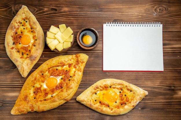 Vista superior de panes de huevo horneados recién salidos del horno en un escritorio de madera marrón, masa, pan de huevo, bollo, desayuno