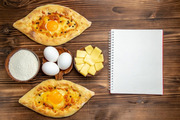 Vista superior panes de huevo horneados recién salidos del horno en el escritorio de madera marrón masa pan de huevo pan de desayuno