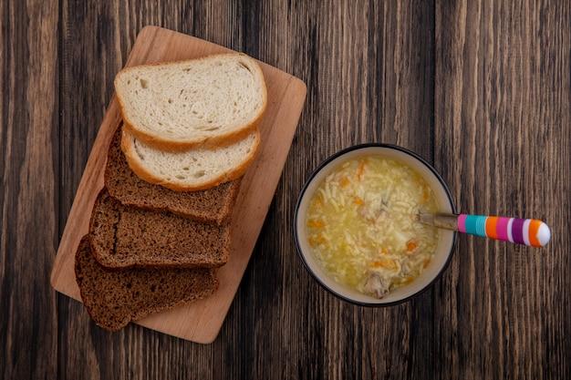 Vista superior de panes en rodajas de centeno y blancos sobre tabla de cortar y tazón de sopa de pollo orzo con cuchara sobre fondo de madera