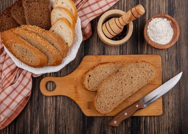 Vista superior de panes en rodajas como centeno de mazorca marrón sin semillas y blancos en un plato sobre tela a cuadros y en una tabla de cortar con un cuchillo, pimienta negra y harina sobre fondo de madera