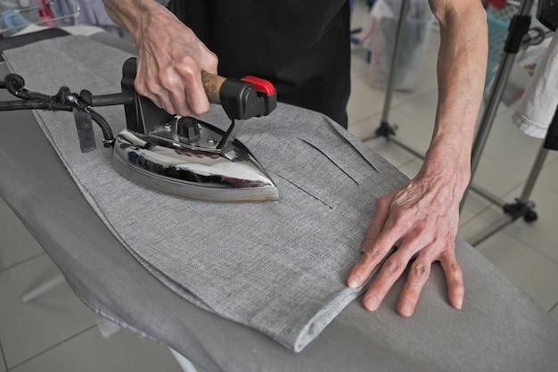 Vista superior del paño que plancha de la mano de la mujer en fondo gris. pantalón de planchado femenino visto arriba.