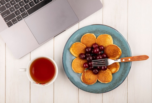 Vista superior de panqueques con cerezas y tenedor en plato con taza de té y bloc de notas sobre fondo de madera