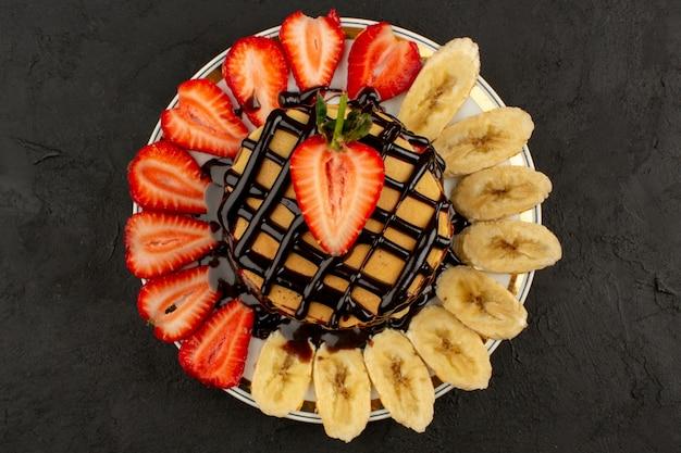 Vista superior panqueques deliciosos con frutas y chocolate en el fondo oscuro