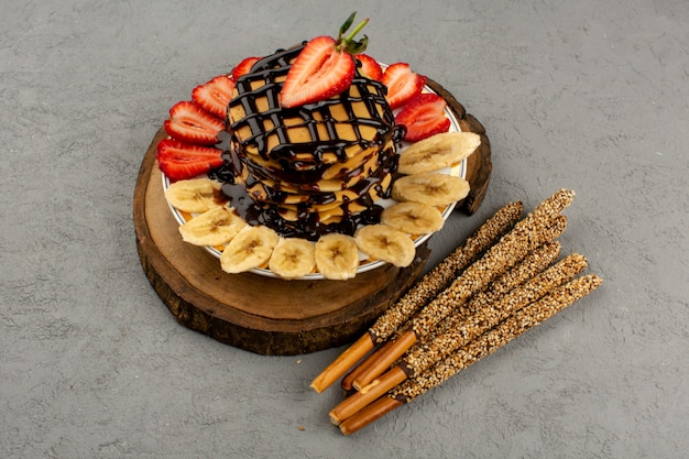 Vista superior panqueques dulce delicioso delicioso con fresas rojas en rodajas y plátanos junto con palitos de caramelo en el gris
