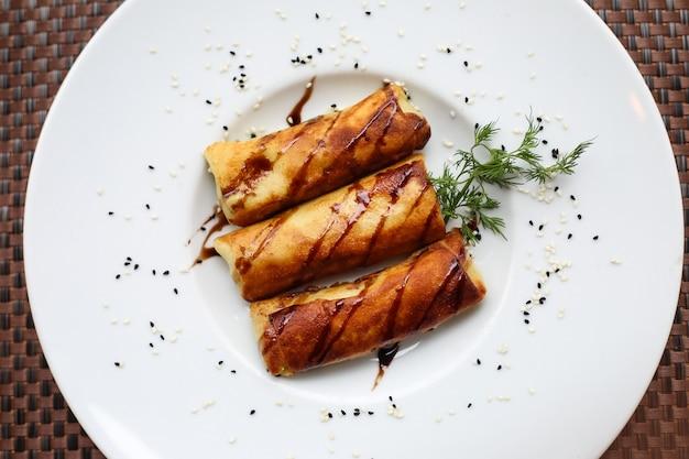 Vista superior panqueques enrollados con salsa y una ramita de eneldo en un plato