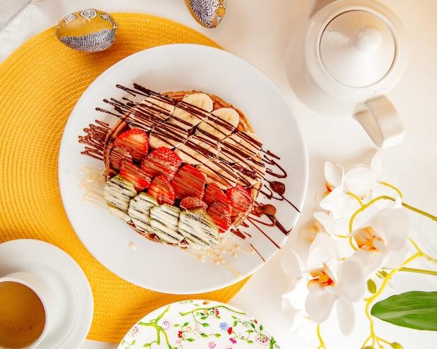 Vista superior de panqueques finos con fresas, plátanos y kiwi cubiertos con salsa de chocolate en un plato blanco