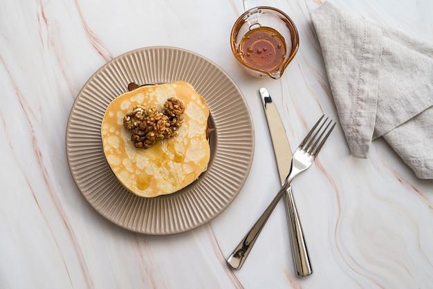 Vista superior de panqueques con miel sobre la mesa