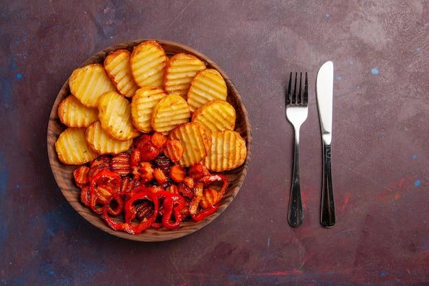 Vista superior de papas al horno con verduras cocidas dentro de la placa en el espacio oscuro