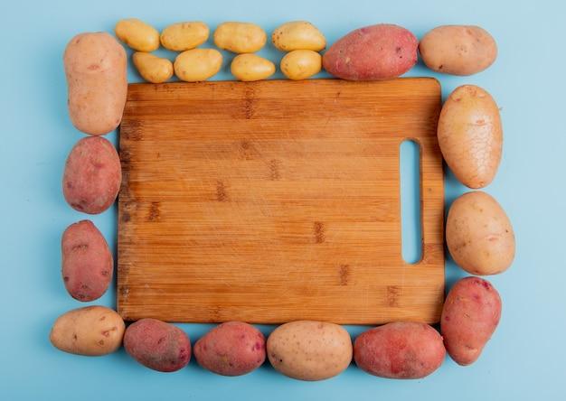 Vista superior de papas alrededor de tabla para cortar sobre superficie azul