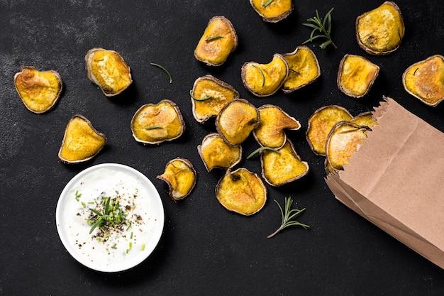 Vista superior de papas asadas con salsa y bolsa de papel