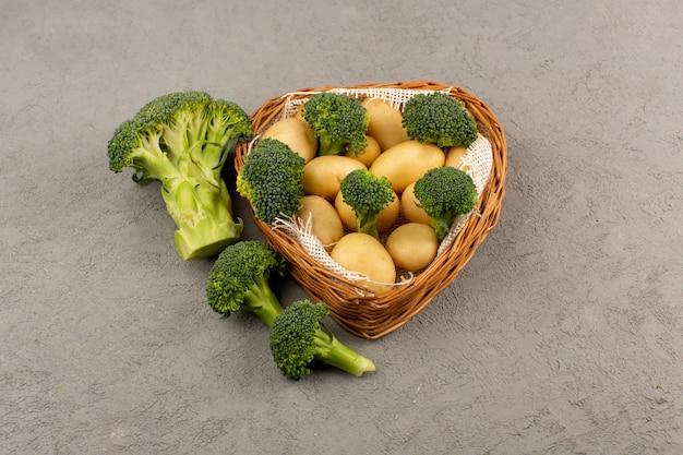 Vista superior de papas y brócoli fresco dentro de la cesta madura en el piso gris